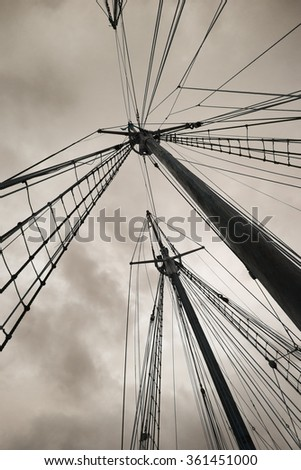 Old boat masts against stormy sky - stock photo