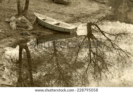 Old boat near the lake with the reflection of the trees on the water. - stock photo