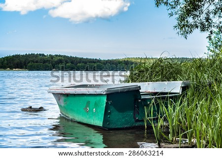 Old boat on the lake at the shore  - stock photo