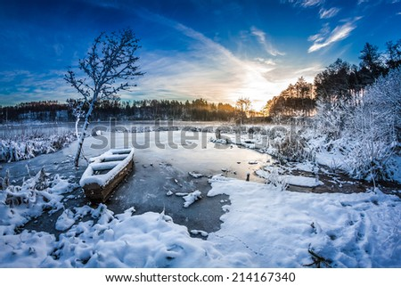 Old boat on the lake covered with snow in winter - stock photo