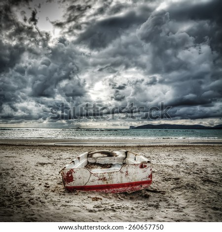 old boat on the sand under a dramatic sky - stock photo