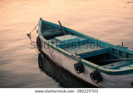 Old boat on the water in sunset light