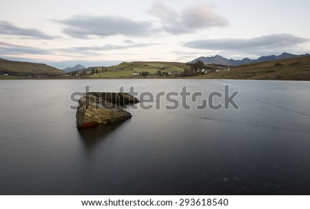 old boat sunk in a loch on the isle of skye - stock photo