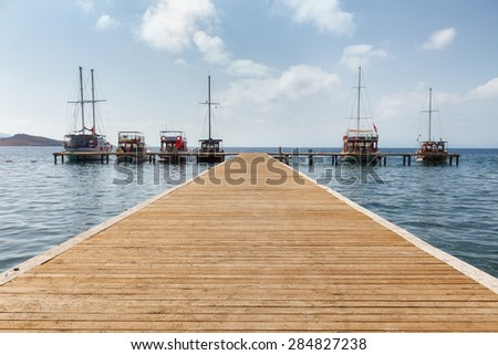 old boats at the end of the pier on the sea - stock photo