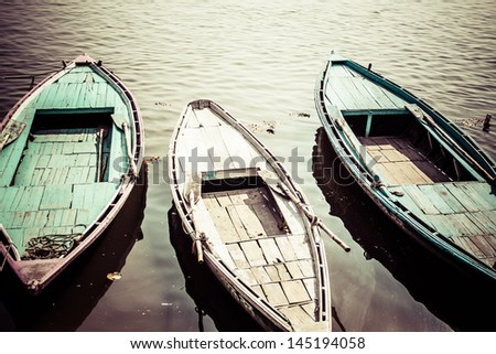 Old boats on brown waters of Ganges river, Varanasi, India - stock photo