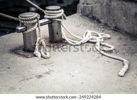 Old bollard with the sea rope. Rope tied in a knot on a bollard in sea harbor. Mooring rope wrapped around the cleat on pier. Mooring equipment - monochrome image. - stock photo