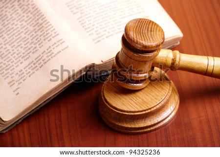 Old book and gavel on wooden desk - stock photo