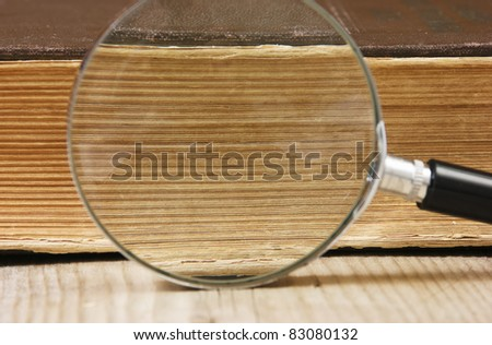 old book and magnifying glass - stock photo