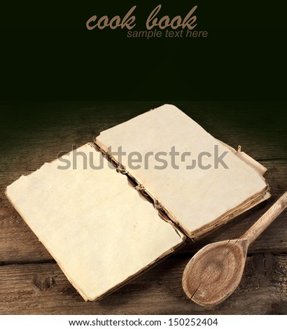 old book and wooden spoon with empty space for text  - stock photo