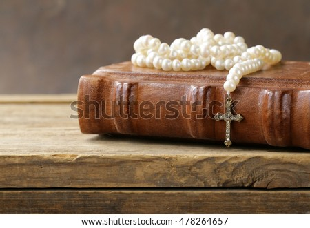 old book (bible) and the Christian symbol cross on pearl necklace