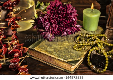 old book, flower, candle and open jewelry box with green necklace still life, renaissance concept with dark grunge light