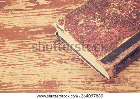 Old book isolated on wooden background - stock photo