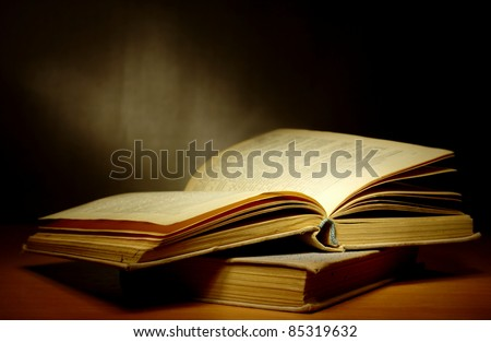 old book on a dark background and light beam - stock photo