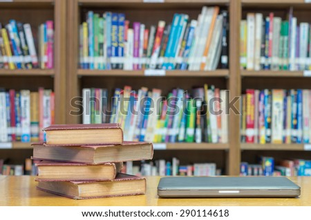 old book on the desk in library with tablet - stock photo
