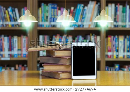 old book on the desk in library with tablet and Luxury lighting decoration - stock photo