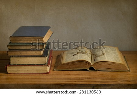 old book open on a wooden table with glasses - stock photo