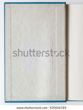 Old book opened to the first page showing a page with a white blank label inside. - stock photo