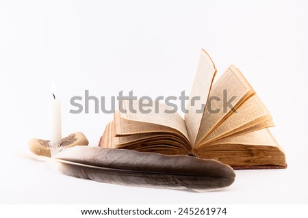 old book pages dissolved, candle and feather on a white background - stock photo