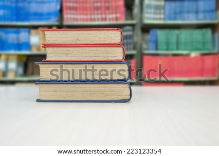 Old book stack on desk in library - stock photo