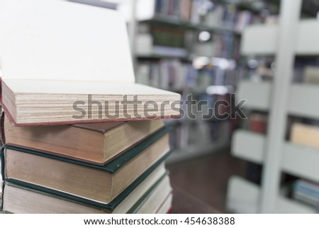 old book stack on wooden table with blur library background