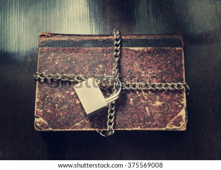 Old book with chain and padlock on table