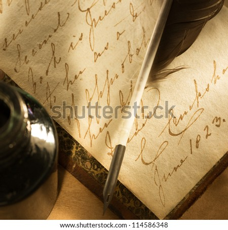 Old book with feather and inkpot - stock photo