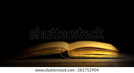 Old book with golden lights - stock photo