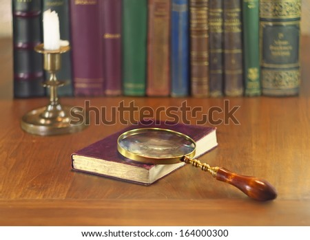 old book with vintage magnifying glass and candle - stock photo