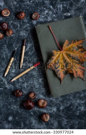 old book with yellow sheet and pencils - stock photo
