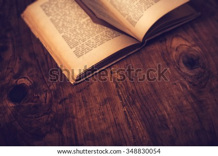 Old book wooden library desk with unreadable text, retro toned image, selective focus - stock photo