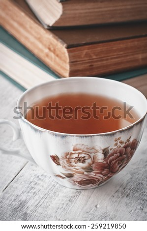Old books and cup of tea on wooden table - stock photo