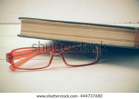 Old books and glasses on a wooden table with filter effect retro vintage styl