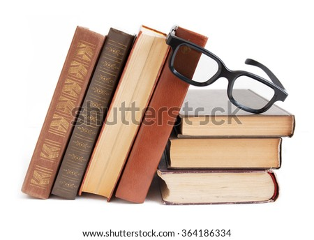 Old books and glasses on book shelf isolated on white background - stock photo
