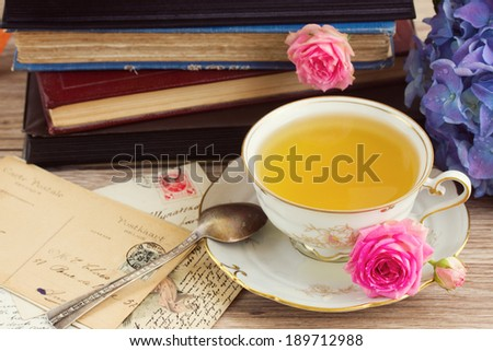 old books and heap of mail with antique cup of tea - stock photo