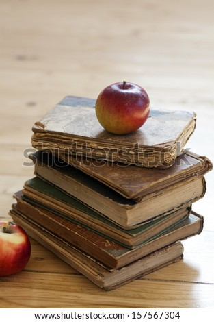 Old books and red apple on wooden background - stock photo