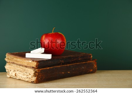 Old books, apple and chalk on blackboard background