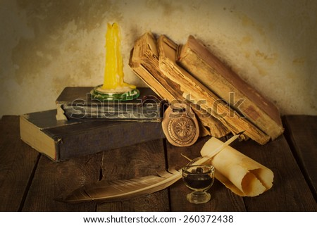 Old books, candle, amulet, pen, ink bottle, roll on the wooden background. Selective focus. Toned photo - stock photo