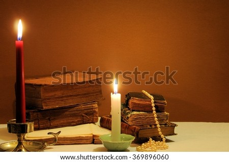 Old books, candles and string of pearls. Selective focus. - stock photo