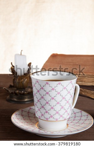 Old books, cup of coffee, candy and ancient candle on the table. Shallow depth of field. Selective focus. - stock photo