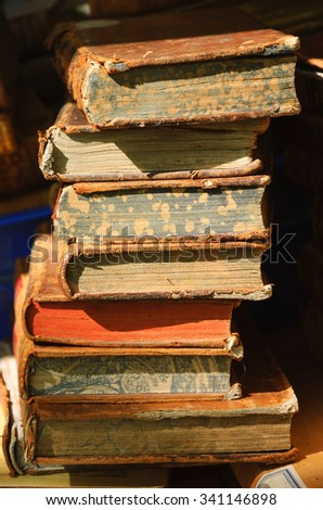 Old books for sale at flea market in Paris (France). A game of light and shadow. Selective focus. - stock photo