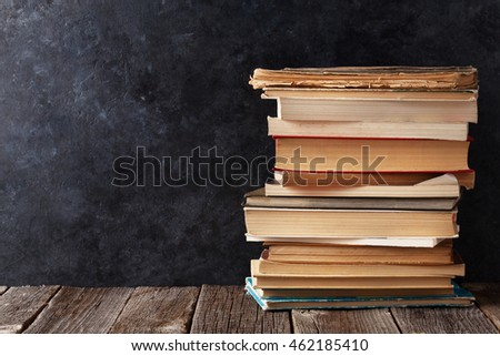Old books in front of classroom chalk board. Back to school concept with copy space