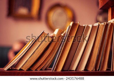 Old books in library shelf - stock photo
