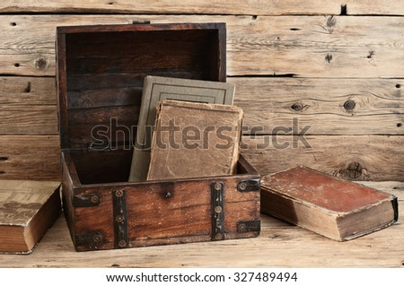 Old books in vintage chest closeup on wooden background. The concept of a chest of knowledge. Free space for text - stock photo