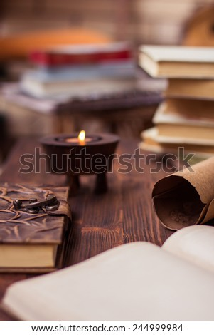 Old books,letter,diary and candle on wooden table - stock photo