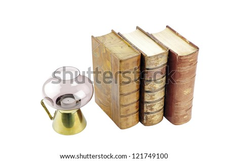 Old books next to a candle - stock photo