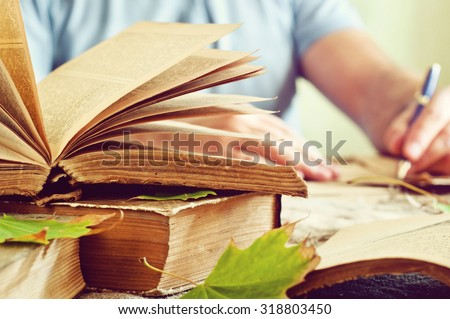 Old books. Old open book close up with autumn leaves on the table. In the background a man hand writing in a notebook. Copy space. Free space for text - stock photo