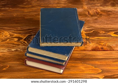 old books on a brown wooden table - stock photo