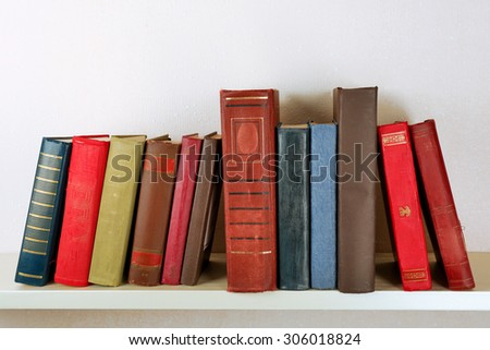 Old books on shelf, close-up, on light wall background - stock photo