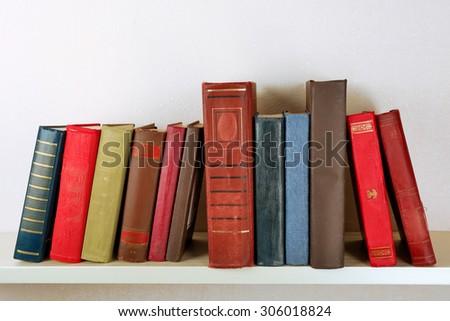 Old books on shelf, close-up, on light wall background - stock photo