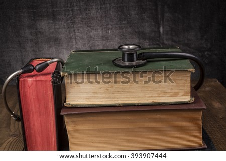 Old Books on Wood Table with Black Stethoscope - stock photo